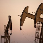 Oil companies shoulder pain of downturn with lower output