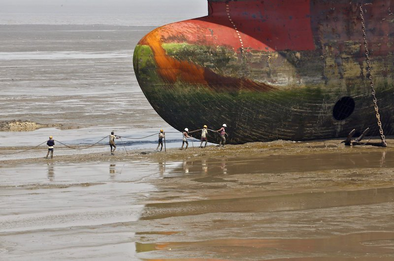 Workers carry a rope line to fasten a decommissioned ship at the Alang shipyard in Gujarat, India, in this March 27, 2015 file photo. The ship recycling industry has been hit by a flood of cheap Chinese steel and new European Union environmental rules due later this year threaten to push business to more modern yards in places like China and Turkey - in turn devastating local economies. To match Insight SHIPBREAKING-SOUTHASIA/ REUTERS/Amit Dave/Files      TPX IMAGES OF THE DAY