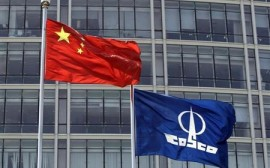 A COSCO company flag and a Chinese national flag fly in front of the company's headquarters in Beijing August 26, 2010. REUTERS/Barry Huang