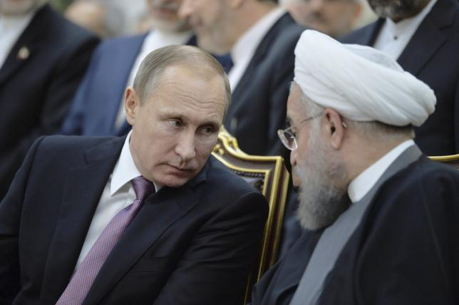 Russian President Vladimir Putin (L) speaks with his Iranian counterpart Hassan Rouhani during a signing ceremony after the talks in Tehran, Iran, November 23, 2015. Alexei Druzhinin/Sputnik/Kremlin via Reuters/File Photo