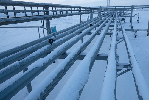 An oil worker walks beside oil cluster well pipework on the Russkoye heavy crude oil field, operated by Rosneft PJSC, in the Yamalo-Nenets region of East Siberia, near Novy Urengoy, in Russia, on Thursday, Dec. 8, 2016. The surprise $11 billion sale of shares in oil giant Rosneft PJSC to Qatar's sovereign wealth fund and Glencore Plc caps a 2016 that's only gotten better for the Russian President Vladimir Putin as the political tide moved in his favor. Photographer: Andrey Rudakov/Bloomberg
