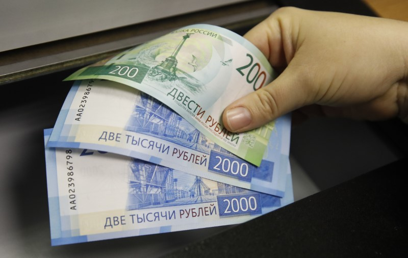 FILE PHOTO - A woman holds new 200 and 2,000 rouble banknotes in a bank in Moscow, Russia November 21, 2017. REUTERS/Maxim Shemetov