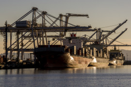 Container ships sit at a berth at the Port of Oakland in Oakland, California, U.S., on Tuesday, Jan. 13, 2015. The trade gap, or the difference in the value of imports and exports, shrank 7.7 percent to $39 billion, the smallest since December 2013, Commerce Department figures showed last week. Photographer: David Paul Morris/Bloomberg
