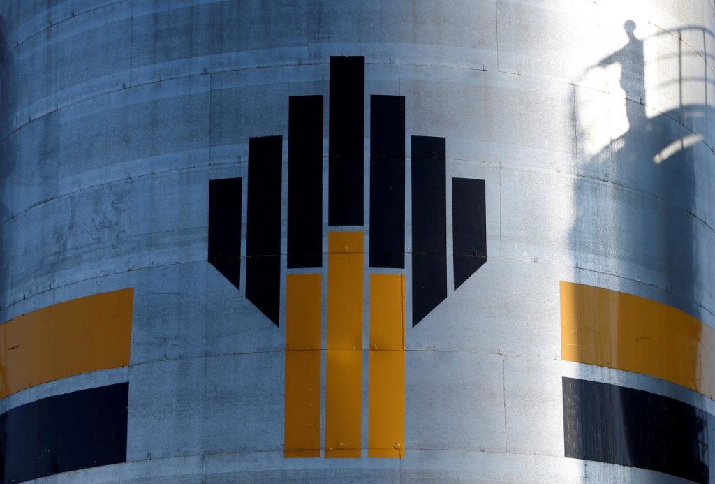 FILE PHOTO - The shadow of a worker is seen next to a logo of Russia's Rosneft oil company at the central processing facility of the Rosneft-owned Priobskoye oil field outside the West Siberian city of Nefteyugansk, Russia, August 4, 2016. REUTERS/Sergei Karpukhin/File Photo