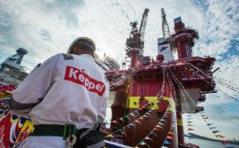A worker stands in front of the Floatel Triumph, a semi-submersible accommodation rig operated by Floatel International Ltd. and developed by Keppel Offshore & Marine Ltd.'s deep water technology group, during a media tour in Singapore, on Friday, March 11, 2016. Keppel Corp., parent company of Keppel Offshore & Marine, is the world's biggest builder of oil rigs. Photographer: Nicky Loh