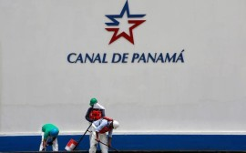 Workers are seen under the logo of the Panama Canal at the Miraflores locks, a day before the inauguration of the Panama Canal Expansion project, in Panama City, Panama June 25, 2016. REUTERS/Alberto Solis