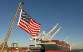 An American flag waves in the foreground at this US port, where a cargo ship loaded with containers is berthed beneath giant cranes on a clear blue sky day. The image symbolizes concepts like Made in America, Made in the USA, industry, global economy, pride, strength, power, patriotism, trade, manufacturing, and the idea of getting back to work.